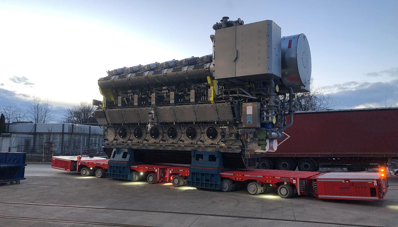 Zwei rote, flache Spezialwagen mit sehr vielen Rädern transportieren einen riesigen Schiffsmotor vor einer Industriehalle.