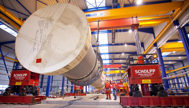 Eine Röhre, fast so lang wie die Industriehalle, in der sie schwebt, hängt an durch Stützen gehaltenen Seilen.