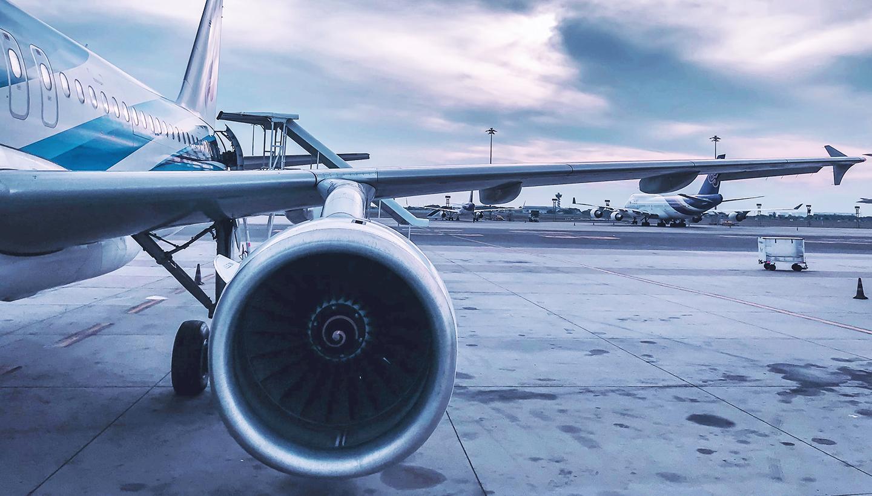 Ein Passagierflugzeug auf dem Flughafen, mit Blick von vorn auf den seitlichen Rumpf und die linke Tragfläche, im Vordergrund das Triebwerk unter dem linken Flügel.