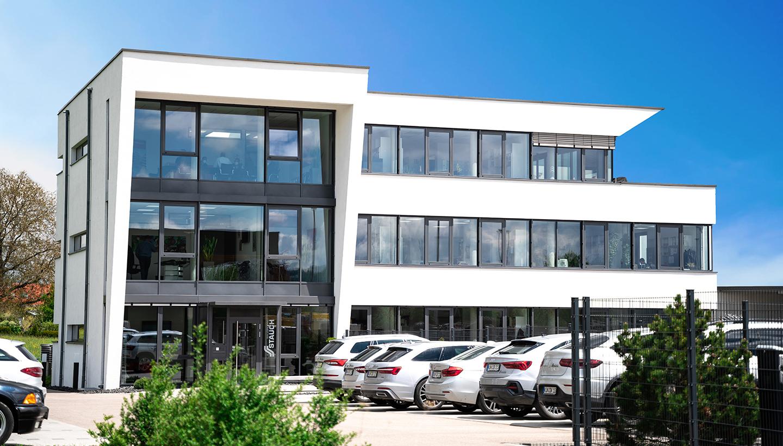 Weißes, modernes Firmengebäude mit großer Glasfront und Blick über davorliegendem Parkplatz.