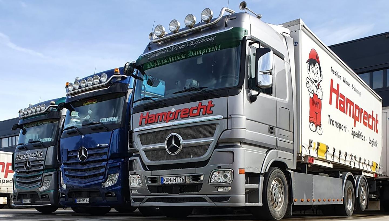 Drei große Mercedes-LKW von schräg unten fotografiert.