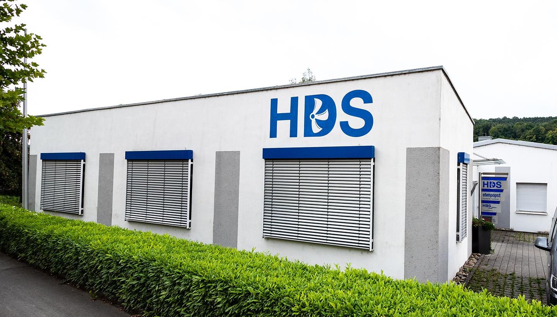 Weißes, einstöckiges Flachdachhaus mit blauem HDS-Schriftzug.