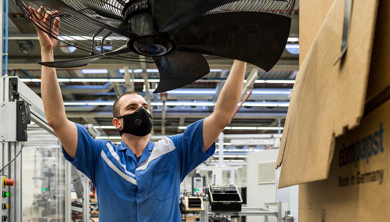 Mitarbeiter im blauen Werkshemd und mit Mund-Nasen-Schutz justiert mit nach oben gestreckten Armen einen großen Ventilator