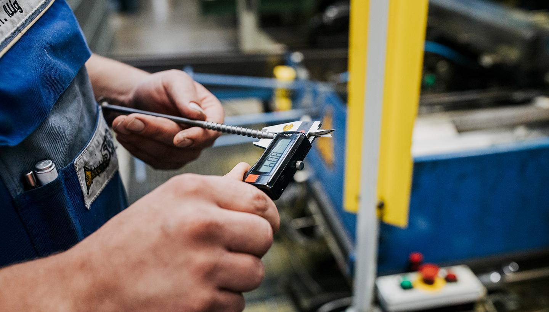 Arbeiter mit Schraube und Messgerät in den Händen