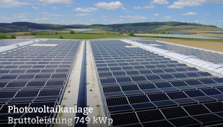 """Bild einer Photovoltaikanlage vor hügeliger Landschaft mit Aufschrift """"Photovoltaikanlage Bruttoleistung 749 kWp"""""""