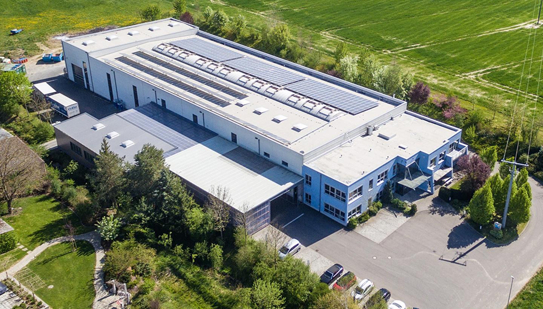 Luftaufnahme eines flachen Firmengebäude, das an eine Wiese angrenzt