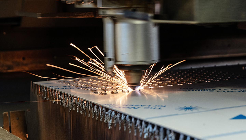 Mittels Laser wird eine Metallplatte funkensprühend bearbeitet