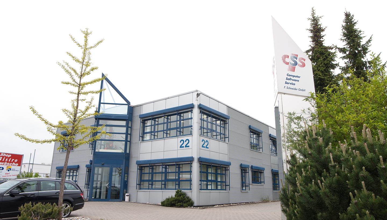 Zweistöckiges Flachdachhaus mit blauen Fenstern und verglastem, metallenem Eingangsvorbau sowie Pylon im Vordergrund mit Aufschrift CSS