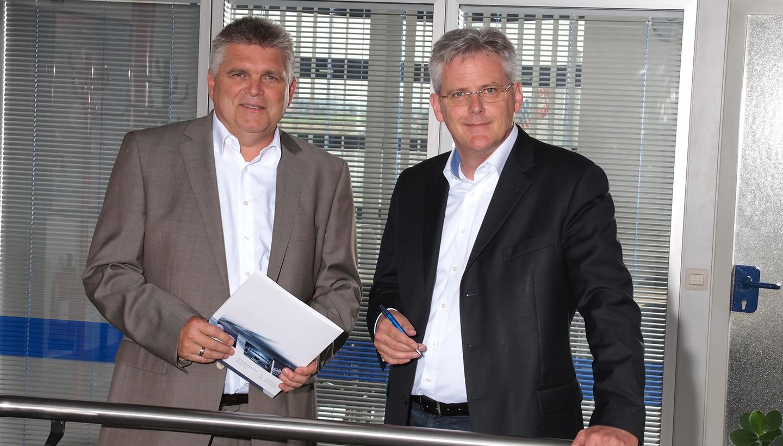 Zwei Männer hinter einem Edelstahlgeländer stehend, links im hellen Anzug, rechts im dunklen Jacket