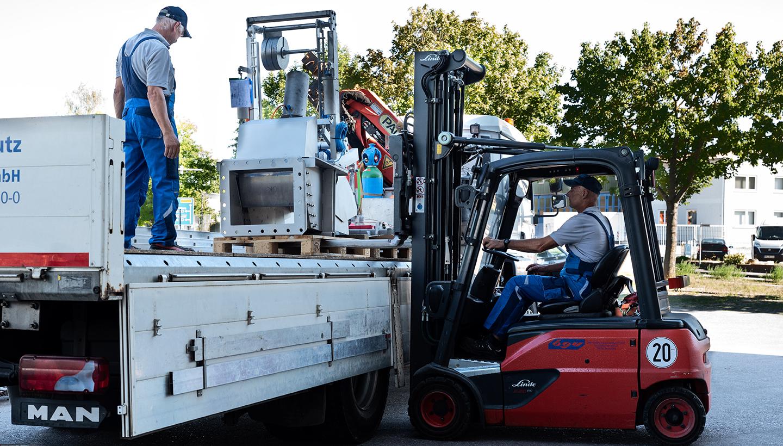Ein Gabelstapler belädt einen LKW, auf dem ein Mann steht, mit einer Edelstahlanlage