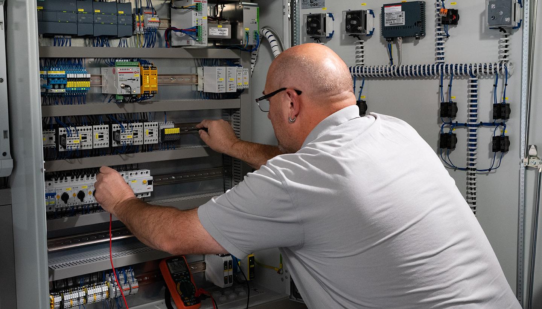 Schräg von hinten links fotografiertes Bild eines leicht vorgebeugten Mannes, der zwei Kontakte eines elektronischen Prüfgerätes an Kontakte in einem geöffneten Schaltschrank hält