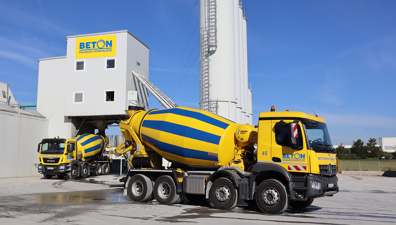 Ein blau-gelbes Betonmischfahrzeug bei der Befüllung und eines bei der Abfahrt im Betonwerk