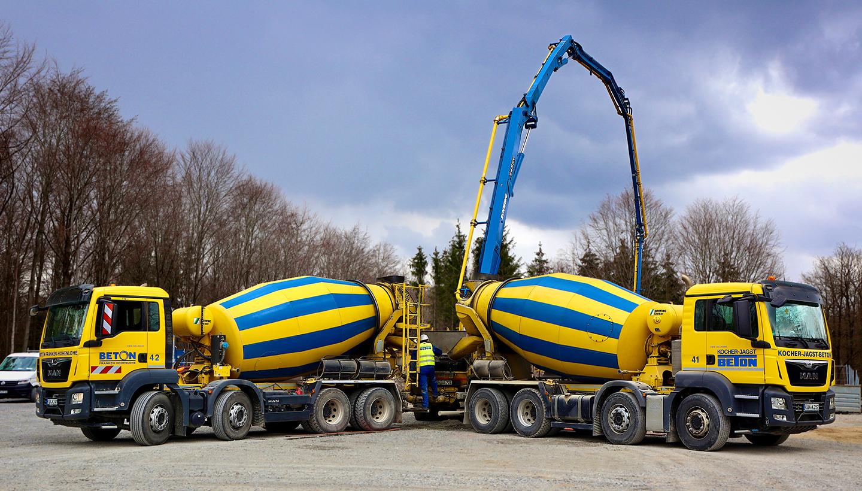Zwei blau-gelbe Betonmischfahrzeuge pumpen auf einem großen Platz Beton ab