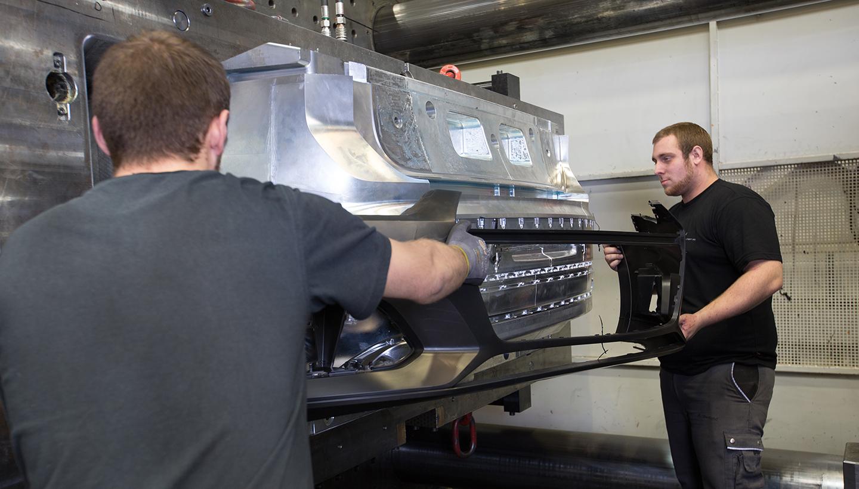 Zwei männliche Mitarbeiter führen ein schwarzes Bauteil einer silbernen Maschine zu