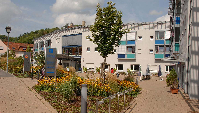 Modernes, zweigeschossiges Gebäude mit überdachten Eingangsbereichen und Pflanzbeeten vor dem Haus.