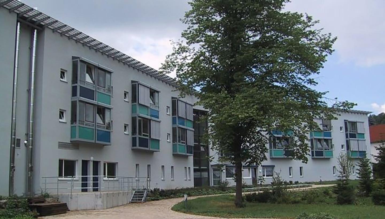 Hinteransicht eines zweigeschossigen Gebäudes mit gepflastertem Weg zwischen Haus und Rasenfläche.