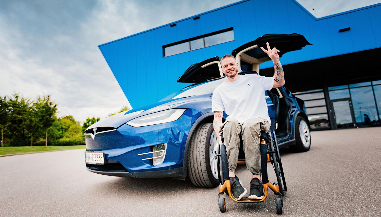Mensch im Rollstuhl freut sich über sein umgebautes Auto