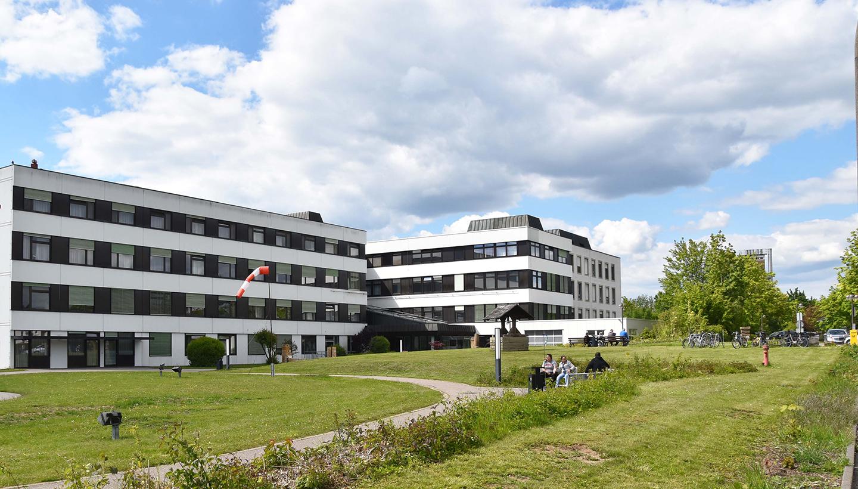 Zwei im rechten Winkel angeordnete, weiße, viergeschossige Flachdachgebäude mit Wiese, Wegen und Bank, auf der Menschen sitzen, im Vordergrund
