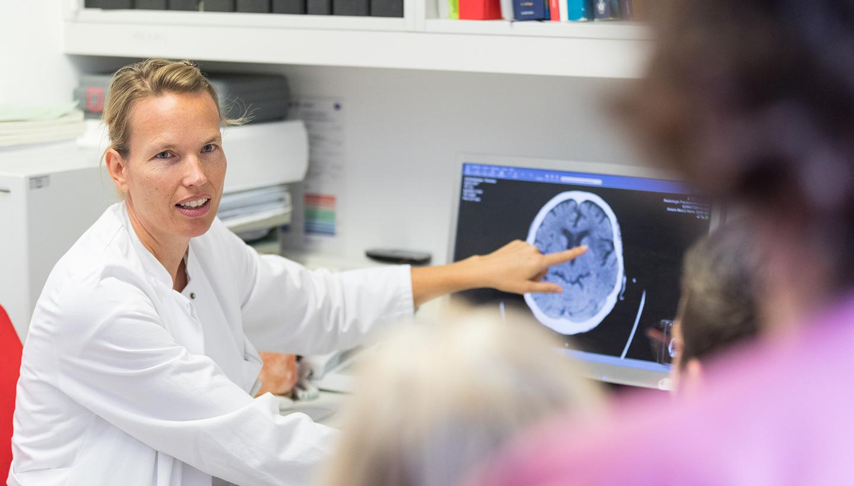 Eine sitzende Frau im weißen Kittel zeigt vor einem schemenhaft von hinten zu erkennendem Erwachsenen mit Kind auf das Bild eines im Monitor sichtbaren, im Querschnitt aufgenommenen, menschlichen Gehirns