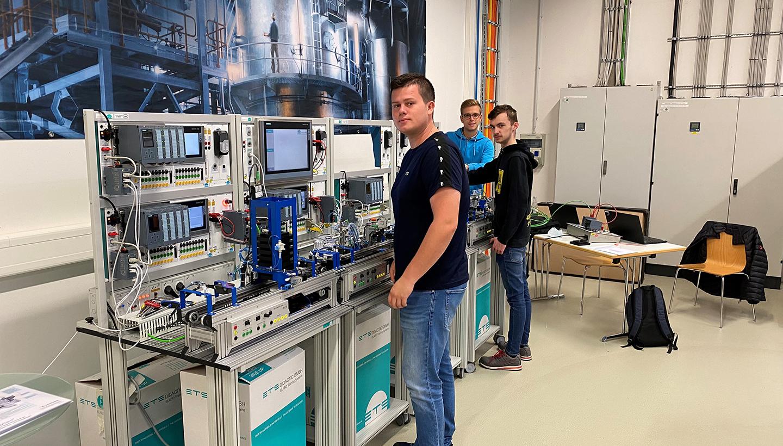 Drei junge Männer an einem technischen Trainingsgerät voller Schalter, Kabel und Monitore