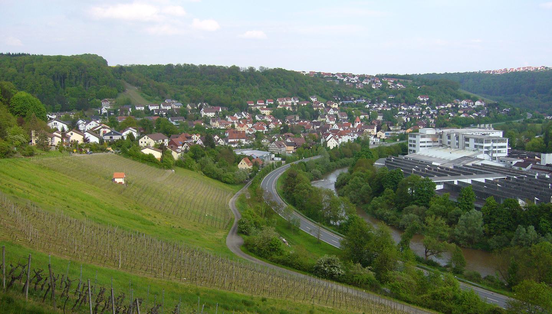 Luftbild einer Gemeinde mit Weinhang im Vordergrund links und Firmengelände mit Werkshallen am rechten Bildrand
