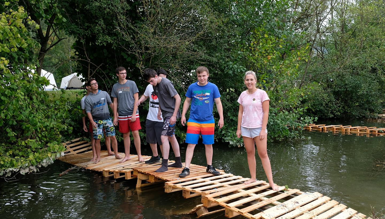 Sieben junge Menschen stehen auf einer aus Europaletten gebauten Behelfsbrücke, die über einen Bach führt