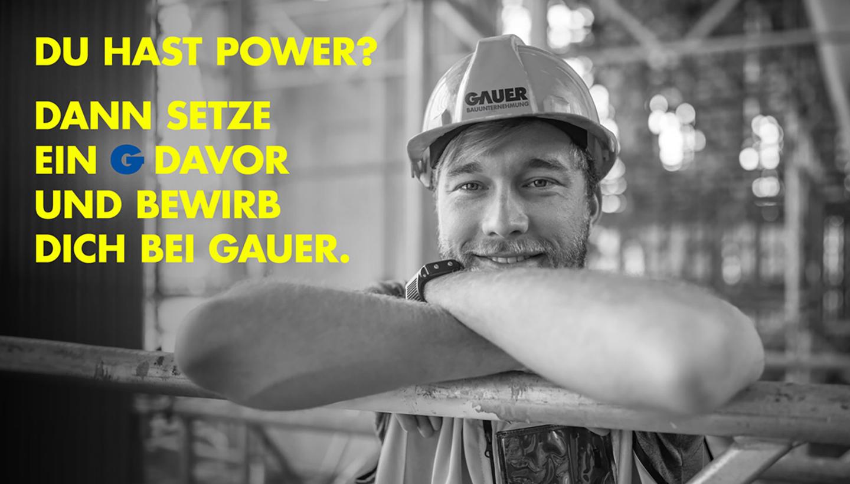 Ein Bauarbeiter lehnt mit verschränkten Armen über eine Mauer, daneben die Worte: Du hast schon Power? Dann setze ein G davor und bewirb dich bei Gauer