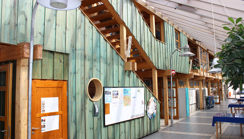 Innenansicht eines lichtdurchfluteten Gebäudeflurs in Holzbauweise