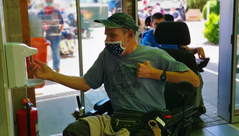 Ein Mann im Rollstuhl nutzt im Flur eines Hauses ein Desinfektionsgerät, dahinter warten weitere Menschen im Rollstuhl