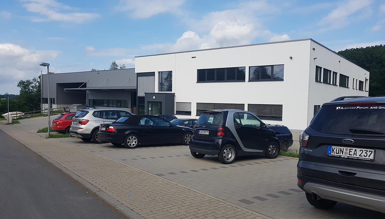 Weißes Firmengebäude mit angeschlossener Halle und Autos auf dem Parkplatz davor