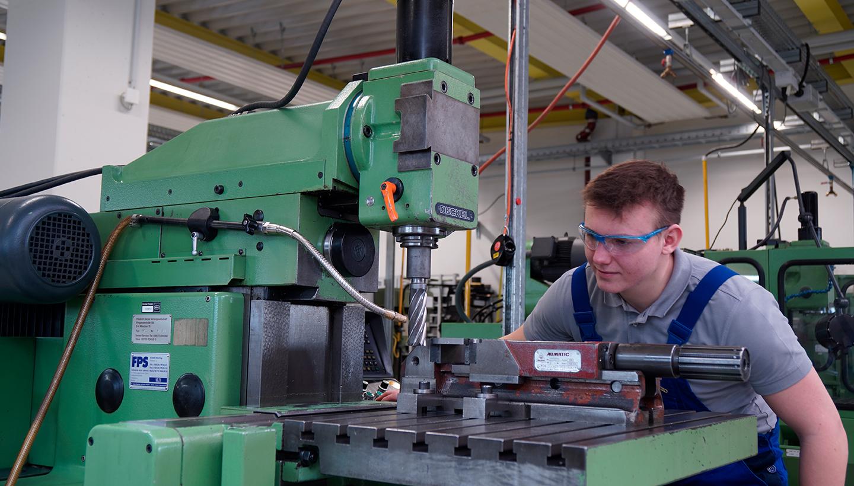 Junger Mann mit Schutzbrille bedient eine, grüne CNC-Fräsmaschine