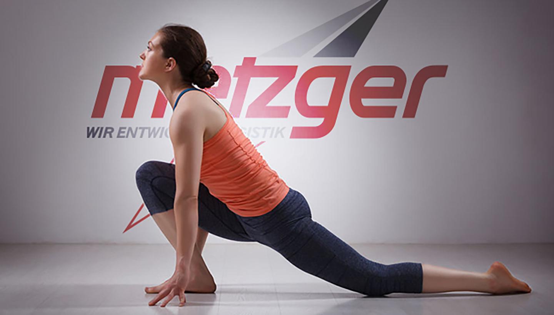 Eine junge Frau in Gymnastikkleidung beim Dehnen im Ausfallschritt vor dem Metzger-Logo
