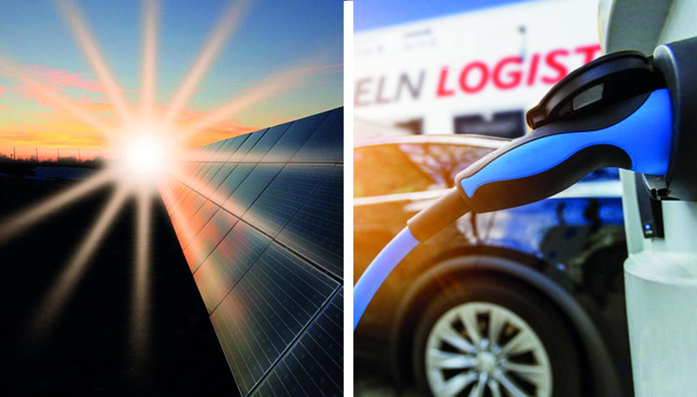 Strahlen der untergehenden Sonne treffen auf Solarflächen (links) und E-Ladeanschluss eines LKWs, dahinter ein PKW vor einem LKW