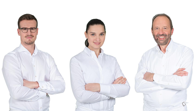 Zwei Männer außen und eine Frau in der Mitte mit weißer Kleidung stehen mit verschränkten Armen nebeneinander und blicken in die Kamera