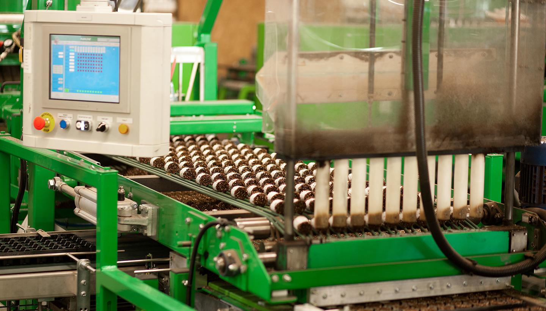 Eine Produktionsanlage für die Easypots des Unternehmens aus Künzelsau mit Transportbändern und Überwachungsmonitor
