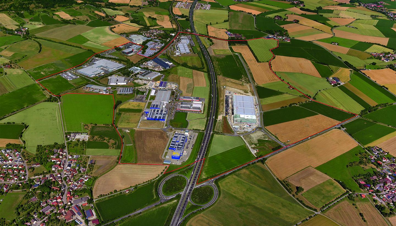 Hier bieten Unternehmen attraktive Arbeitsplätze: Luftbild eines Gewerbegebietes, durch das eine große Straße führt