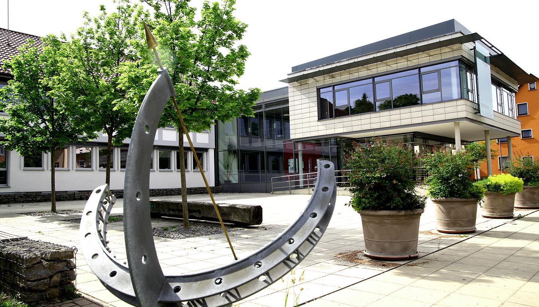 Rathausvorplatz mit Rathaus und mit Sonnenuhr im Vordergrund. Die Gemeindeverwaltung bietet sichere und moderne Arbeitsplätze