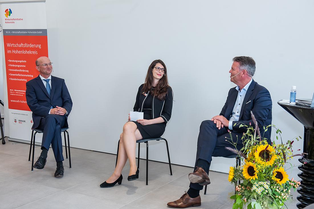 Drei Personen, auf Stühlen sitzend, vor einer weißen Wand im Gespräch; links und rechts je ein Mann im dunklen Anzug, in der Mitte eine Frau im dunklen Kostüm