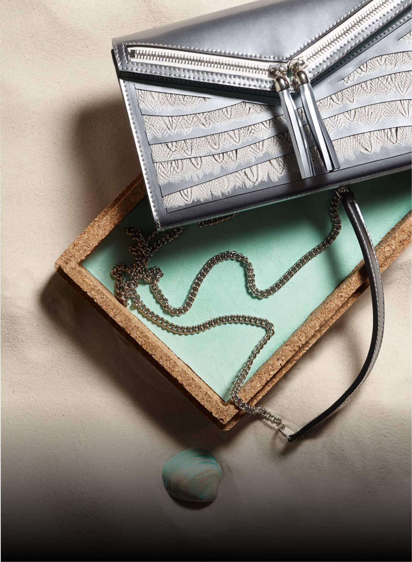 Pochette argentée haute couture Neptune Ingrid Paris + boitier sur sable fin