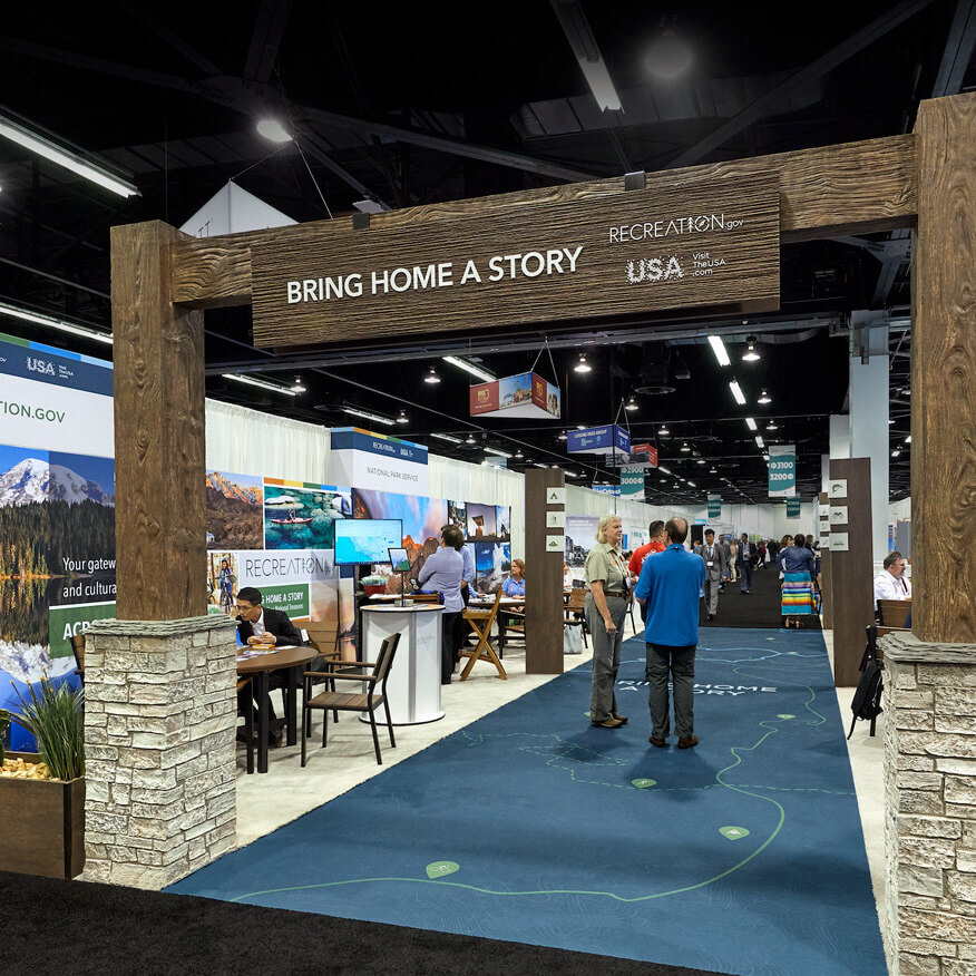 """Photo of a tradeshow display which reads """"Bring Home a Story""""."""