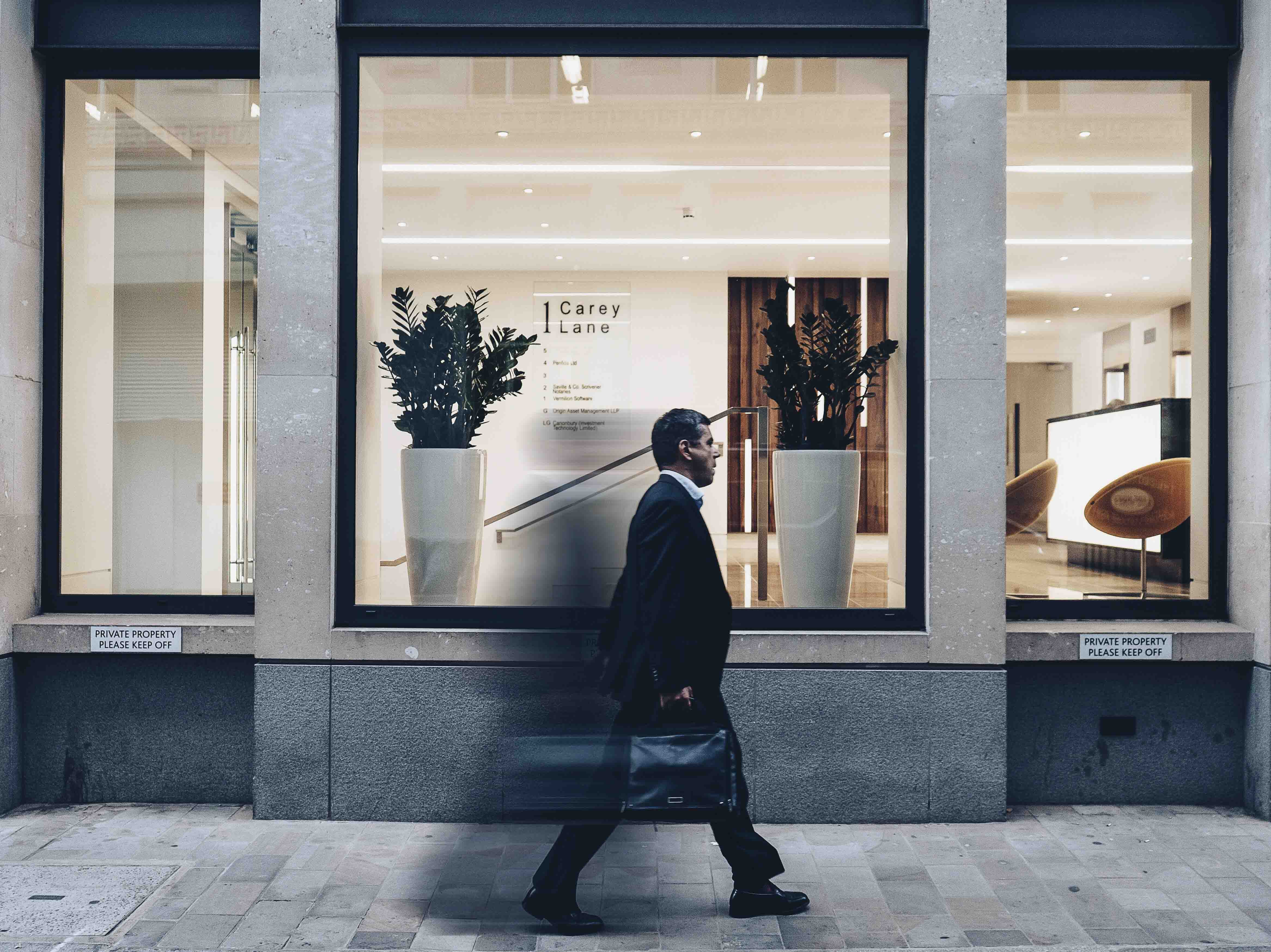 Business man walking quickly past a shop.