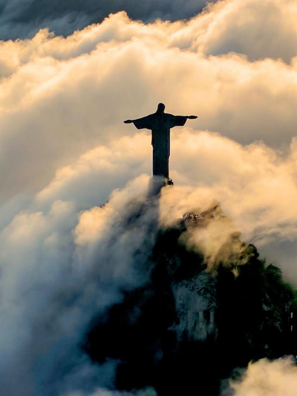 Foto do Cristo Redentor envolto por nuvens na cidade do Rio de Janeiro, RJ.