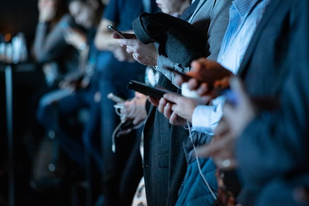 Foto. Pessoas segurando e olhando para seus smartphones.
