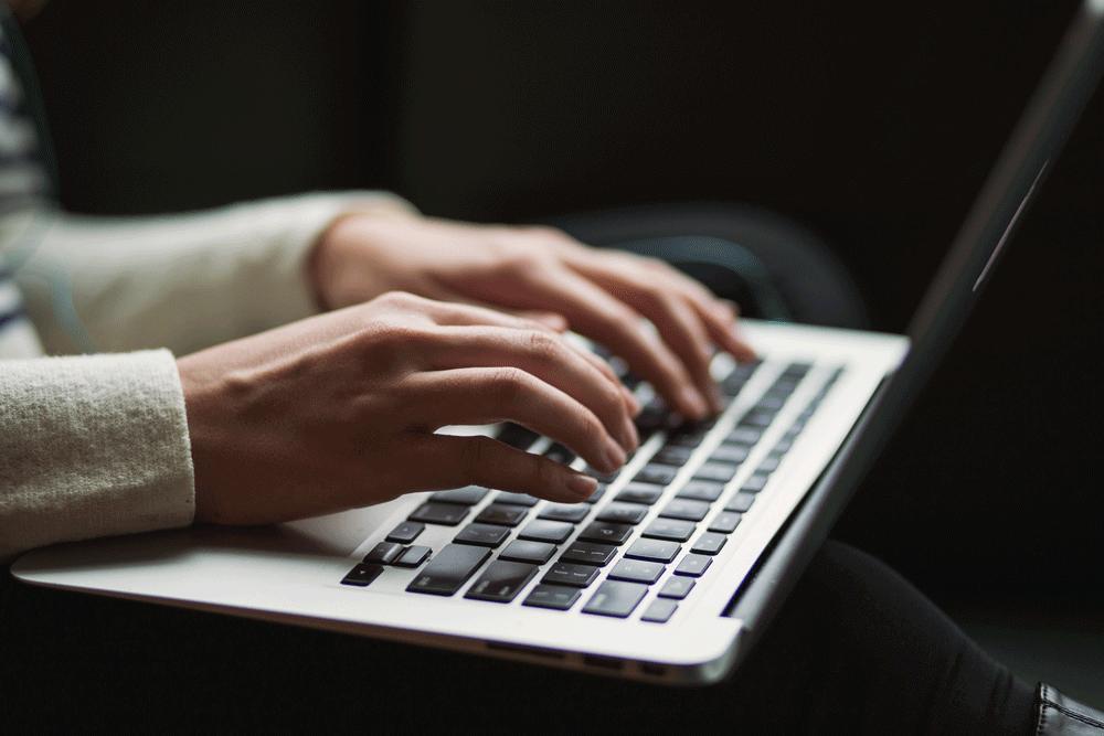 Due mani che digitano sulla tastiera di un computer portatile