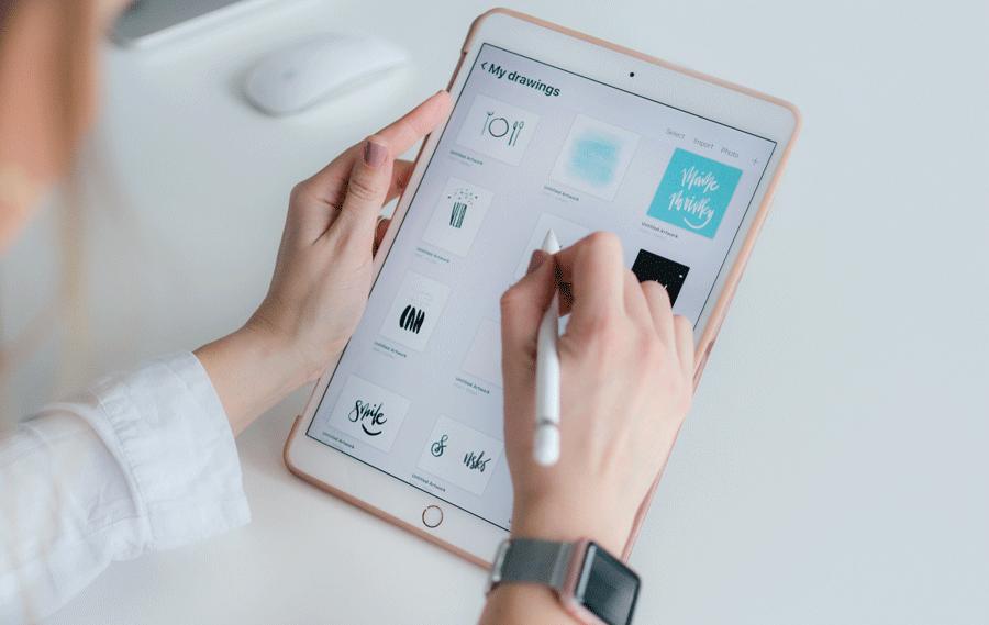 Due mani femminili con smalto rosa che reggono un iPad ed una penna