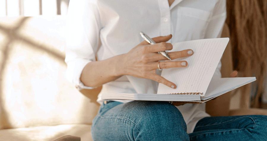 Due mani femminili con una penna in mano che sfogliano un quaderno