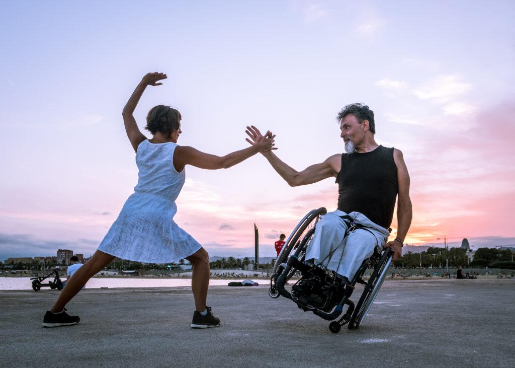 Donna con vestito bianco in piedi che tende la mano ad un uomo in sedia a rotelle in equilibrio su una sola ruota