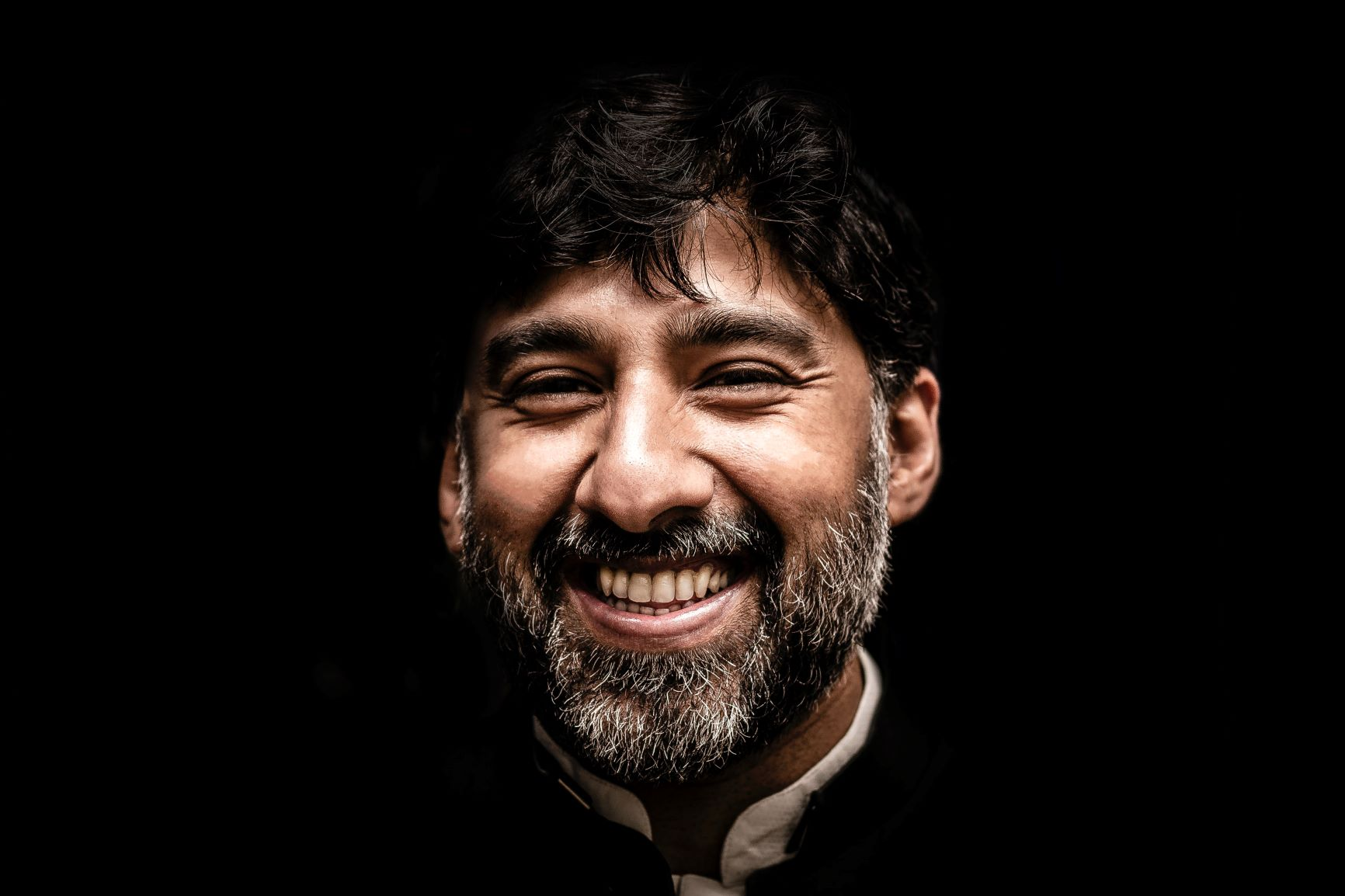 Man smiling with black background