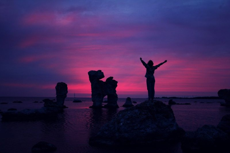 person standing on a rock overlooking the ocean with their hands up for digital marketing