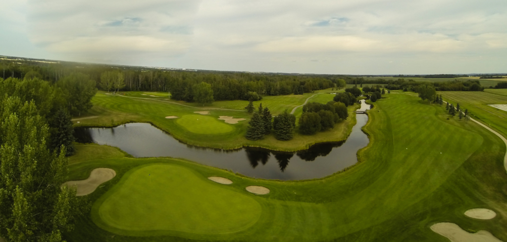 Aerial shot of a green golf course with a long and narrow water hole.